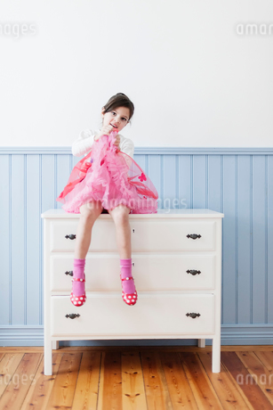 Sweden, Little girl (4-5) in pink dress sitting on dresserの写真素材 [FYI02202633]