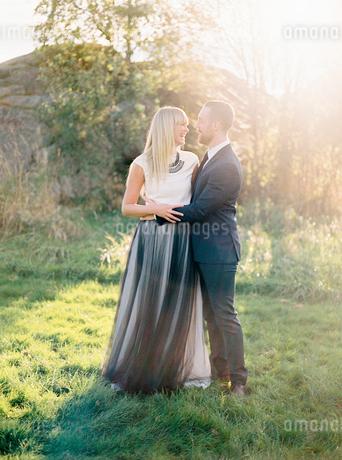 Sweden, Groom and bride standing together in grassの写真素材 [FYI02202665]