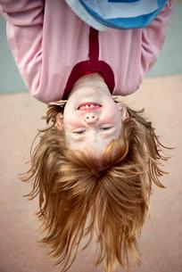 Sweden, Redhead girl (4-5) hanging upside downの写真素材 [FYI02202666]