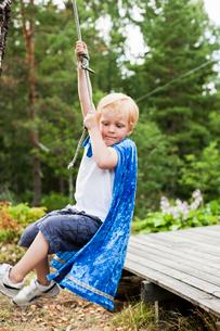 Sweden, Sodermanland, Stockholm Archipelago, Musko, Boy (4-5) swinging on ropeの写真素材 [FYI02202677]