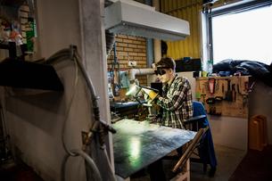 Sweden, Young man welding metalの写真素材 [FYI02202689]