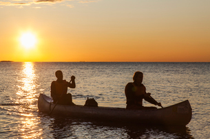 Sweden, Medelpad, Sundsvall, Essvik, Brattberget, Two men in canoe at sunsetの写真素材 [FYI02202716]