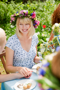 Young woman with flower wreath sitting at picnic table and holding man's handの写真素材 [FYI02202741]