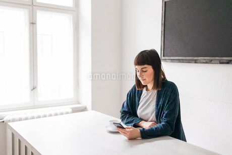 Sweden, Young woman using mobile phone at desk in officeの写真素材 [FYI02202754]