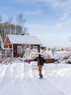 Finland, Pohjanmaa, Pietarsaari, Kruunupyy, Man cleaning yard with snow pusherの写真素材 [FYI02202768]