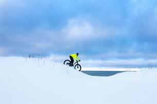 Finland, Pohjanmaa, Pietarsaari, Man cycling in snowの写真素材 [FYI02202774]