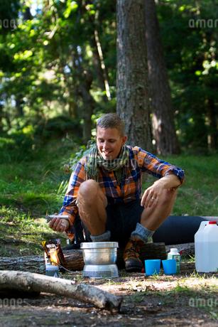 Sweden, Ostergotland, Agelsjon, Hiker preparing food on camping stoveの写真素材 [FYI02202780]