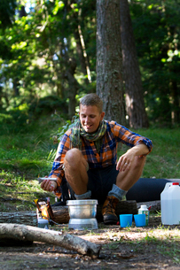 Sweden, Ostergotland, Agelsjon, Hiker preparing food on camping stoveの写真素材 [FYI02202780]