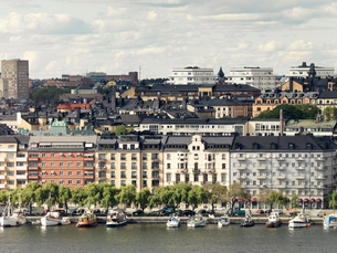 Sweden, Stockholm, Waterfront cityscape with nautical vessels moored in foregroundの写真素材 [FYI02202782]