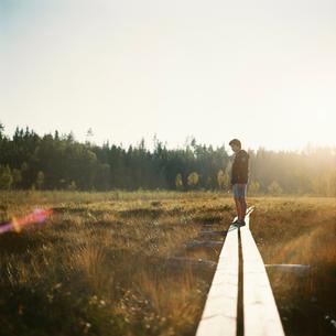 Sweden, Vastmanland, Bergslagen, Hallefors, Silvergruvan, Boy (12-13) standing on overpass going thrの写真素材 [FYI02202817]