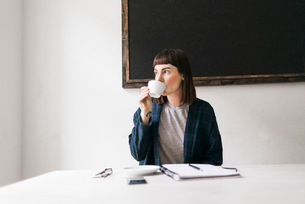 Sweden, Young woman drinking coffee in officeの写真素材 [FYI02202825]