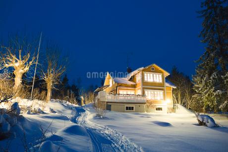 Sweden, Stockholm Archipelago, Uppland, Loparo, View of illuminated house in winterの写真素材 [FYI02202853]