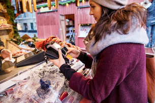 Sweden, Stockholm, Gamla Stan, Woman paying with credit card at marketの写真素材 [FYI02202862]