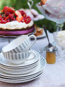 Sweden, Tea cups and plates on table with cake in backgroundの写真素材 [FYI02202904]
