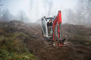 Sweden, Uppland, Nacka, Woman using phone in bulldozerの写真素材 [FYI02202911]