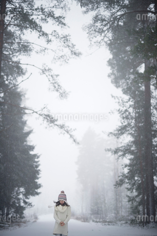 Sweden, Vastmanland, Bergslagen, Girl (8-9) in winter forestの写真素材 [FYI02202946]