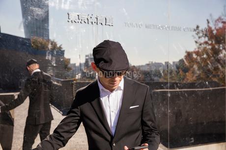 Japan, Tokyo, Shibuya, Man standing outside building, using phoneの写真素材 [FYI02202957]