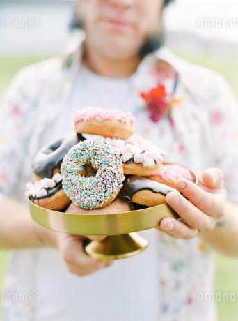 Sweden, Groom holding doughnuts at hippie weddingの写真素材 [FYI02203046]