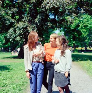 Sweden, Stockholm, Ostermalm, Three women walking through parkの写真素材 [FYI02203052]