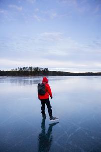 Sweden, Dalarna, Lintjarnen, Woman ice skating on frozen lakeの写真素材 [FYI02203060]