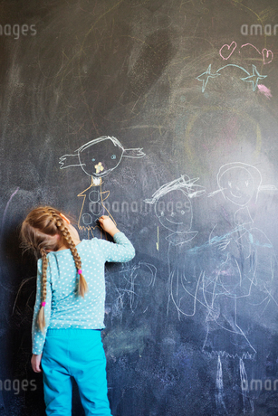 Finland, Girl (4-5) drawing on chalkboardの写真素材 [FYI02203067]