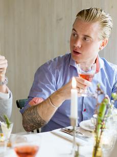 Sweden, Tattooed man raising glass of wineの写真素材 [FYI02203077]