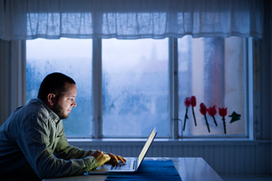 Finland, Man sitting at table and using laptopの写真素材 [FYI02203113]