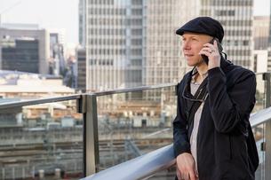 Japan, Tokyo, Shibuya, Man leaning against balustrade, talking on phoneの写真素材 [FYI02203133]