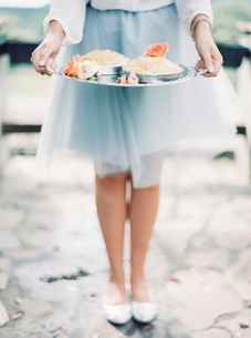 Italy, Woman in elegant skirt holding silver tray with dessertの写真素材 [FYI02203156]