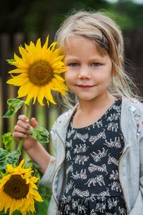 Sweden, Portrait of girl (4-5) with sunflowerの写真素材 [FYI02203157]