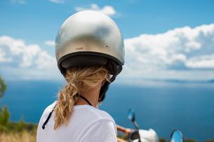 Croatia, Blonde woman wearing crash helmet against seaの写真素材 [FYI02203175]