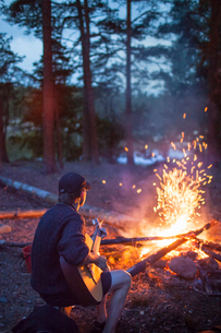 Sweden, Medelpad, Man playing guitar by campfireの写真素材 [FYI02203186]