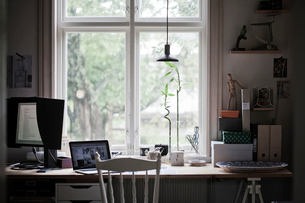 Sweden, Desk with laptop and computer monitor by windowの写真素材 [FYI02203229]