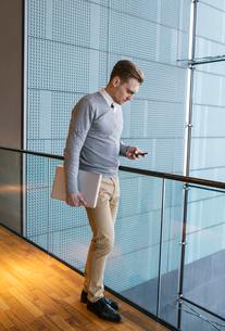 Finland, Young businessman using phone in office buildingの写真素材 [FYI02203241]