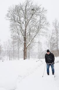 Sweden, Vastmanland, Bergslagen, Hallefors, Silvergruvan, Mature man clearing snowの写真素材 [FYI02203242]