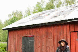 Sweden, Varmland, Filipstad, Gasborn, Horrsjon, Woman in rain in front of red barnの写真素材 [FYI02203294]