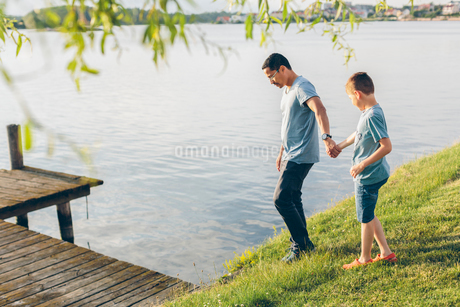 Sweden, Blekinge, Karlskrona, Father and son (8-9) by lakeの写真素材 [FYI02203296]
