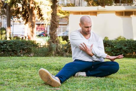 Israel, Tel Aviv, Man sitting on grass and stretchingの写真素材 [FYI02203315]