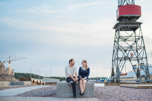 Finland, Varsinais-Suomi, Turku, Couple sitting on block and talking at construction siteの写真素材 [FYI02203337]