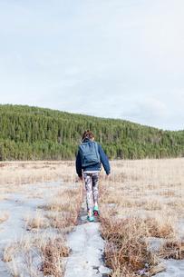 Sweden, Vastmanland, Bergslagen, Hallefors, Ormtjarn, Girl (10-11) with backpack walking in dried meの写真素材 [FYI02203343]