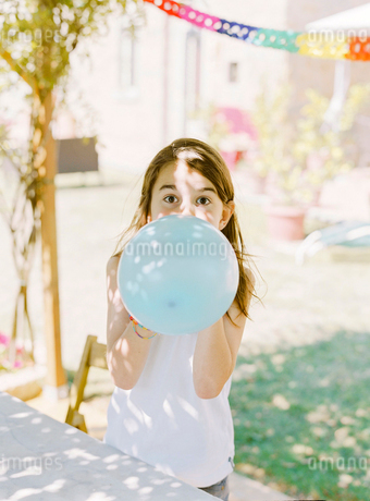 Italy, Boy (8-9) inflating blue balloonの写真素材 [FYI02203345]