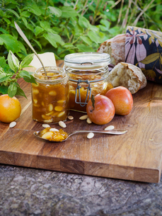 Sweden, Plum marmalade with almonds, plums and bread on cutting boardの写真素材 [FYI02203372]