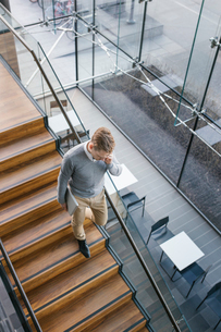 Finland, Young businessman walking downstairs and talking on phoneの写真素材 [FYI02203392]