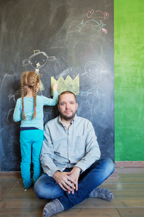 Finland, Girl (4-5) standing by father and drawing on chalkboardの写真素材 [FYI02203396]