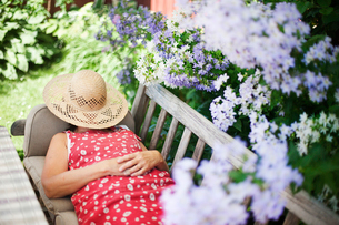 Sweden, Vastergotland, Fristad, Woman lying on bench in domestic gardenの写真素材 [FYI02203405]