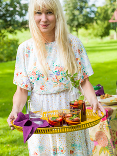 Sweden, Skane, Woman holding yellow tray with sangriaの写真素材 [FYI02203410]