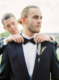 Sweden, Groom adjusting partner´s bow tie at gay weddingの写真素材 [FYI02203440]