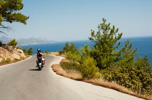 Greece, Karpathos, Couple riding motor scooter along road over seaの写真素材 [FYI02203445]