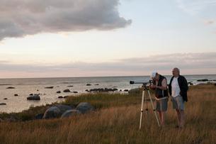 Sweden, Oland, Byxelkrok, Men with telescope by sea at duskの写真素材 [FYI02203447]
