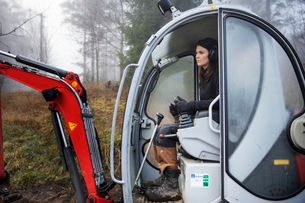 Sweden, Uppland, Nacka, Woman driving bulldozer in forestの写真素材 [FYI02203448]